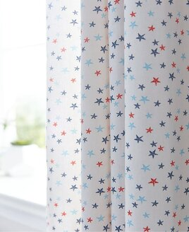 White curtains patterned with small red, blue and pale blue stars.