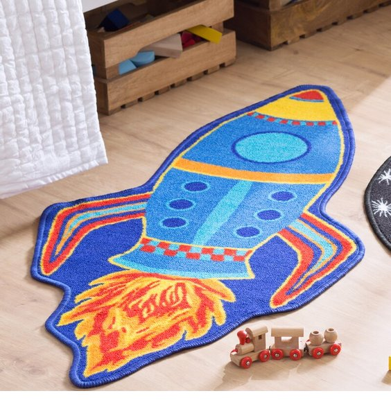 Blue and yellow space rocket shaped rug, powered by a tailf of fire.