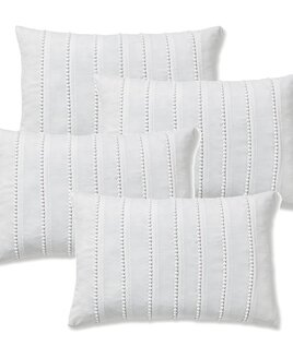 Small white, oblong bolster cushion covers with rows of small pom pom details.