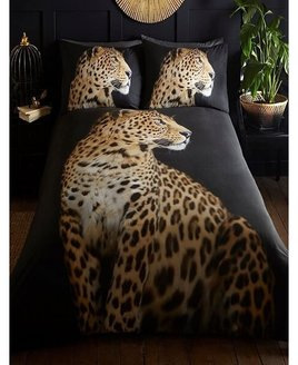 Full size, photographic quality image of a  leopard on a black background. The pillowcases show the leopard's head.